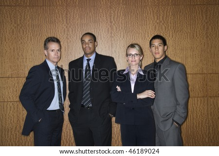 Ethnically diverse businessmen and a businesswoman stand in a lineup as they look towards the camera. Horizontal shot. - stock photo