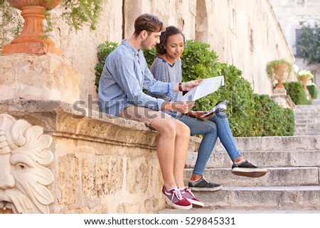 Ethnically diverse couple sitting on a stone wall in a monument sight seeing destination city sharing a map on a summer holiday, recreation outdoors. Travel lifestyle, tourist young man and woman.