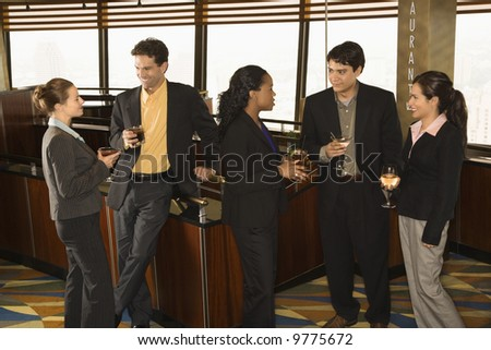 Ethnically diverse group of businesspeople in bar drinking and conversing.