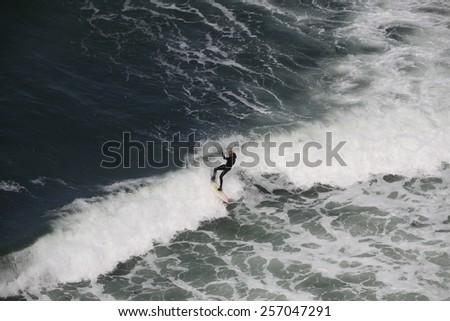 ETRETAT, FRANCE - AUGUST 23, 2010: man surfing at the waves of the Nort-Sea for Etretat, Normandy, France