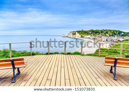 Etretat panoramic view landmark, balcony, beach and village under a cloudy sky. Normandy, France, Europe. - stock photo