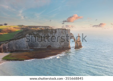 Etretat steep arch shaped cliff at low tide and sunset, view from above, Normandy, France