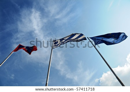 EU and Greece flags against clear blue sky - stock photo