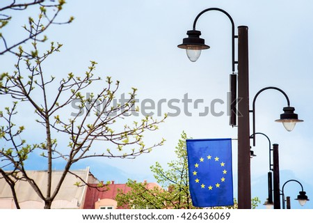 EU flag in old european city - stock photo