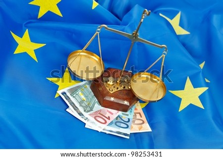 EU flag with money and scale of justice - stock photo