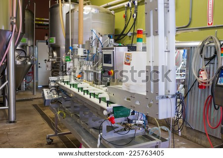 EUGENE, OR - JULY 17, 2014: Can and bottle filling machine on an assembly line at Oakshire Brewing.