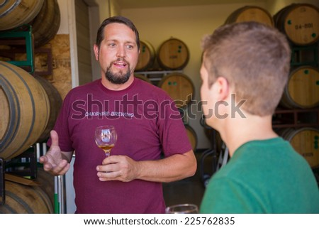 EUGENE, OR - JULY 17, 2014: Master brewer and employee sampling and tasting limited edition bourbon barrel aged beers at Oakshire Brewing. - stock photo