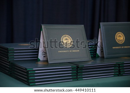 EUGENE, OR - JUNE 12, 2016: University of Oregon graduation diplomas stacked on a table on stage before a commencement ceremony.