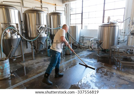 EUGENE, OR - NOVEMBER 4, 2015: Brewery owner Brandon Woodruff cleaning the floor at the startup craft brewery Mancave Brewing. - stock photo