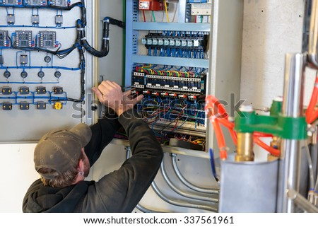EUGENE, OR - NOVEMBER 4, 2015: Electrician working on an electrical output control panel at the startup craft brewery Mancave Brewing. - stock photo