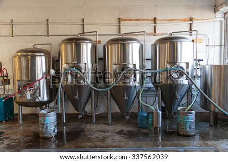 EUGENE, OR - NOVEMBER 4, 2015: Stainless steel commercial beer fermenter at the startup craft brewery Mancave Brewing. - stock photo