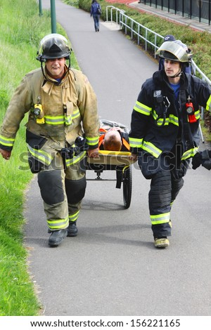 Eugene, Oregon, USA Â?Â? May 2, 2012: Eugene, OR Emergency Services and National Guard work in a disaster response drill. The unidentified firemen are transporting unidentified injured to landing zone. - stock photo
