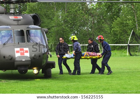 Eugene, Oregon, USA Â?Â? May 2, 2012: Eugene, OR Emergency Services and National Guard work in a disaster drill. Unidentified firemen carried injured person to load on helicopter. - stock photo