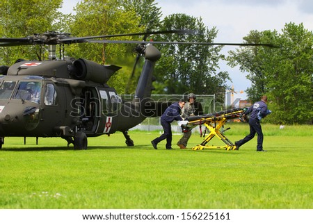 Eugene, Oregon, USA  May 2, 2012: Eugene, OR Emergency Services and National Guard work in a disaster drill. The unidentified firemen are returning from transferring an injured person on helicopter. - stock photo