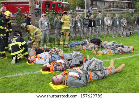 EUGENE, OREGON, USA  May 2, 2012: Eugene, OR the local Emergency Services and National Guard work together in a disaster drill. The firemen are reviewing the injury status cards on the injured. - stock photo