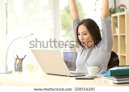 Euphoric and surprised winner winning online watching a laptop at home - stock photo