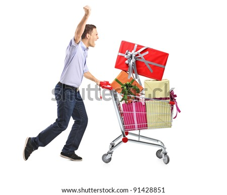 Euphoric male pushing a shopping cart full with gifts isolated on white background