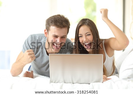 Euphoric marriage winning using a laptop lying on a bed at home - stock photo