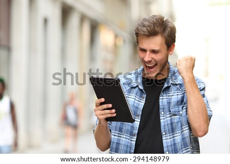 Euphoric winner man screaming with a tablet in the street - stock photo
