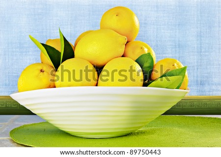 Eureka Lemons in a White China Bowl Sitting On Kitchen Counter ~ Background Is Textured Plaster Wall with Blue Sponge Antiqued Grunge Faux Paint Treatment - stock photo