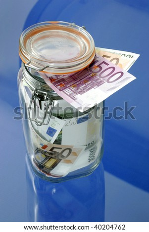 Euro bank notes in a glass jar on blue background