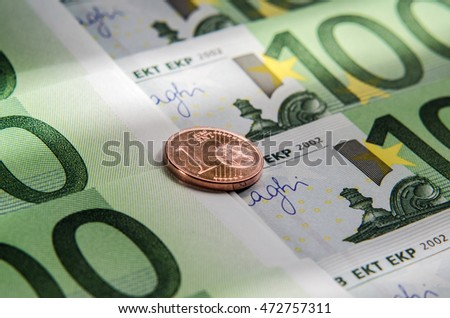 Euro banknotes and coin of one cent. Macro. Background.