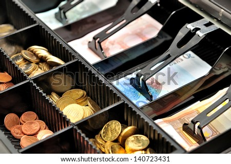 Euro banknotes and coins in a cash box. - stock photo