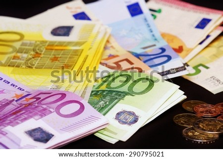 Euro banknotes and coins on a table - stock photo