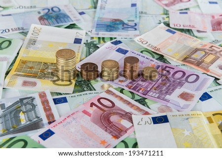 Euro banknotes and euro coins in simple example of unpredictable prognoses. - stock photo