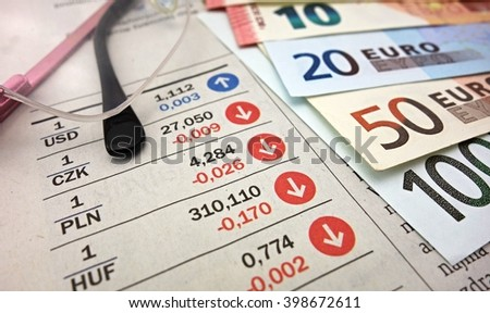 Euro banknotes and glasses on the newspaper