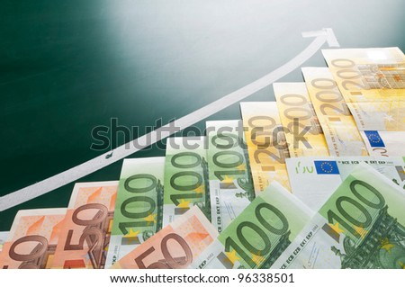Euro banknotes and growing arrow on blackboard - stock photo
