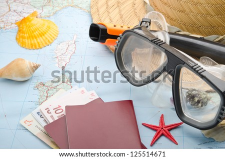 Euro banknotes and passport on a map with snorkel mask - stock photo