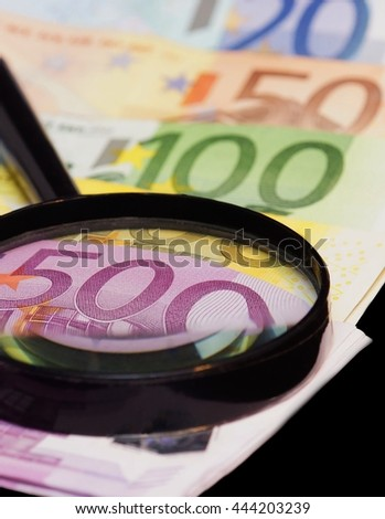 Euro banknotes are under a large magnifying glass - stock photo