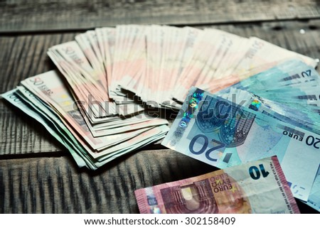 Euro banknotes. Background with european cash money on wooden background. Image toned. - stock photo