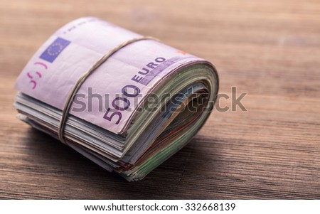Euro banknotes. Euro currency. Euro money. Close-up Of A Rolled Euro Banknotes On Wooden table - stock photo
