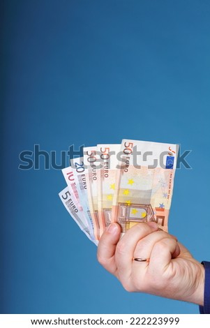 Euro banknotes in male hand on blue background - stock photo