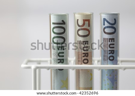 Euro banknotes in Test tubes on white background, health care costs concept - stock photo