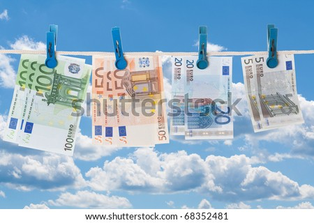 Euro banknotes on a clothesline against cloudy sky - stock photo