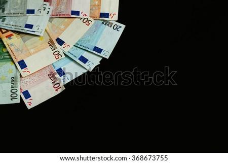Euro banknotes on black background - stock photo
