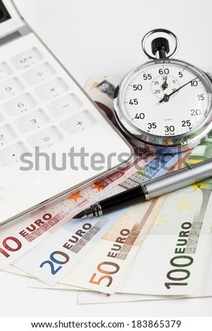 Euro banknotes on white background with white calculator and silver analog stopwatch and fountain pen - stock photo