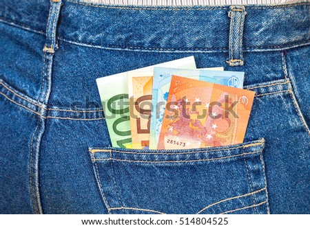 Euro banknotes sticking out of the blue jeans pocket. Money for travel and shopping