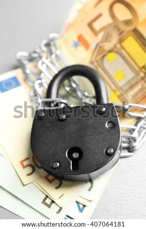 Euro banknotes with lock and chain on gray background - stock photo