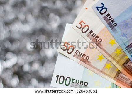 Euro banknotes with shining silver background - 100, 50, 20 euros