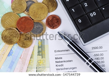 Euro bill and Coins with ballpoint pen, chart and calculator - stock photo