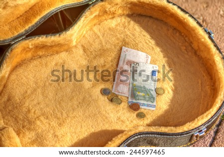 euro bills and coins in a guitar case in the street. Hdr tone mapping effect. - stock photo