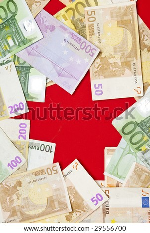 Euro bills on red background,recorded above them.
