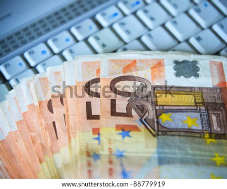 euro cash over the computer keyboard - stock photo