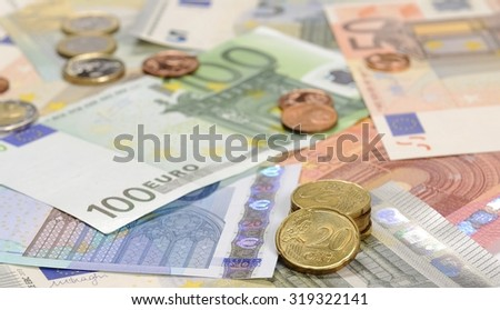 Euro cents on the euro banknotes, cash, shallow DOF - stock photo