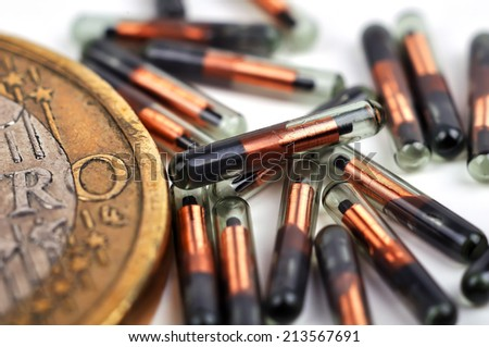 euro coin and animal id implants, close up - stock photo