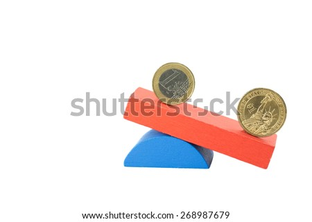 Euro coin and the US one dollar coin stand on the swing from wooden color blocks. Swing is on the side with the US dollar below. - stock photo